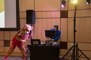 dj and mascot dancing and mixing music at company party