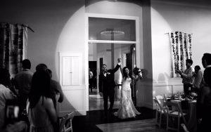 bride and groom in spotlight on wedding day
